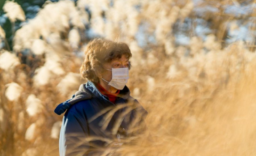 woman wearing a mask in the middle of a field of tan grass