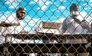 two men cooking on a grill through a chain link fence